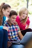 Gente joven que mira la computadora portátil junto Fotografía de archivo