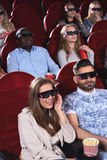 Gente joven que mira la película 3D en el teatro de película Fotos de archivo libres de regalías