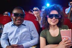 Gente joven que mira la película 3D en el teatro de película Foto de archivo libre de regalías
