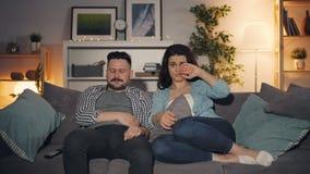 Gente joven que mira película triste en sentarse gritador de la TV en el sofá en el apartamento almacen de video