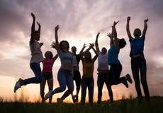 Gente joven que salta contra el cielo de la puesta del sol Foto de archivo