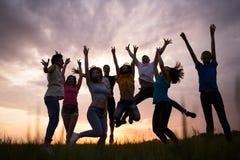 Gente joven que salta contra el cielo de la puesta del sol Fotografía de archivo libre de regalías
