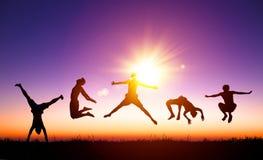 Gente joven que salta en la colina con el fondo de la luz del sol Imágenes de archivo libres de regalías
