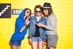 Gente joven que se divierte delante de la pared de ladrillo amarilla Fotografía de archivo