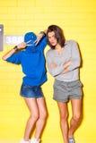 Gente joven que se divierte delante de la pared de ladrillo amarilla Foto de archivo