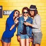 Gente joven que se divierte delante de la pared de ladrillo amarilla Imagen de archivo