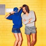 Gente joven que se divierte delante de la pared de ladrillo amarilla Imagenes de archivo