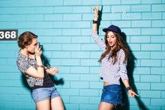 Gente joven que se divierte delante de la pared de ladrillo azul clara Foto de archivo libre de regalías