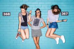 Gente joven que se divierte delante de la pared de ladrillo azul clara Fotos de archivo libres de regalías