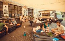 Gente joven que se encuentra para la bebida en restaurante móvil durante festival al aire libre de la comida de la calle Imágenes de archivo libres de regalías