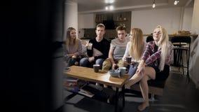 Gente joven que se sienta en canapé y la TV de observación almacen de video