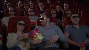Gente joven que se sienta en el cine que mira la película 3D y que come las palomitas metrajes