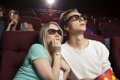 Gente joven que se sienta en el cine, mirando una película y comiendo p Foto de archivo