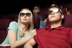 Gente joven que se sienta en el cine, mirando una película y comiendo p Foto de archivo libre de regalías