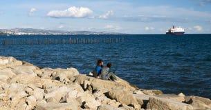 Gente joven que se sienta en el embarcadero pedregoso Fotografía de archivo libre de regalías