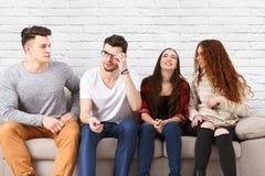 Gente joven que se sienta en el sofá, en casual Foto de archivo
