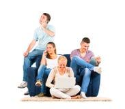 Gente joven que se sienta en el sofá con sus artilugios Foto de archivo