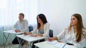 Gente joven que se sienta en la tabla que trabaja en la asignación de escuela en sala de clase metrajes