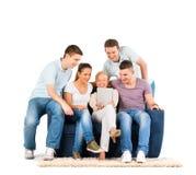 Gente joven que se sienta en un sofá, mirando una tablilla Foto de archivo