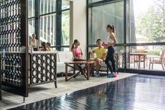Gente joven que socializa en el área del salón de un club de salud de moda imagen de archivo
