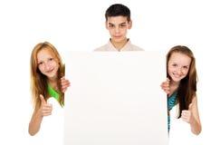 Gente joven que sostiene un cartel en blanco de la publicidad Imagenes de archivo