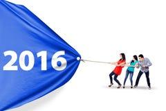 Gente joven que tira de la bandera con los números 2016 Imágenes de archivo libres de regalías