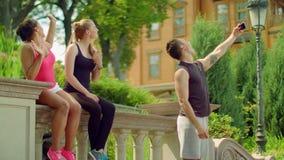 Gente joven que toma el selfie con el teléfono en el parque en verano Amigos felices metrajes