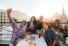 Gente joven que toma el selfie en partido del tejado Foto de archivo libre de regalías