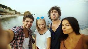Gente joven que toma selfies en la playa almacen de metraje de vídeo