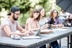 Gente joven que trabaja en el café al aire libre foto de archivo libre de regalías