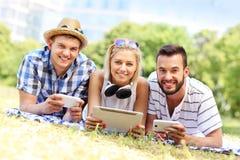 Gente joven que usa la tableta y smartphones en el parque Imágenes de archivo libres de regalías
