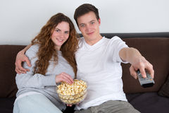 Gente joven que ve la TV y que come las palomitas Imágenes de archivo libres de regalías