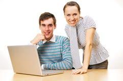Gente joven sonriente con la computadora portátil Fotos de archivo libres de regalías