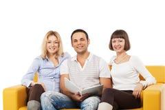 Gente joven sonriente que se sienta junto Foto de archivo