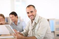 Gente joven sonriente que trabaja en la oficina Fotos de archivo