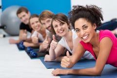 Gente joven vivaz que se resuelve en el gimnasio Imágenes de archivo libres de regalías