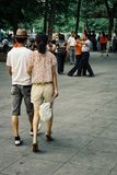 gente joven waling en un parque mientras que gente que baila en el fondo imagen de archivo