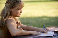 Gente joven y educación, muchacha que estudia para la prueba de la universidad Imagen de archivo libre de regalías