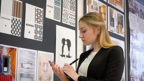 Gente joven y pequeña empresa, mujer caucásica en el trabajo como diseñador, mirando bosquejos de la nueva colección en creativo almacen de video