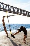 Gente juguetona joven que entrena con el trx cerca del mar por la mañana Foto de archivo libre de regalías