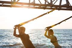 Gente juguetona joven que entrena con el trx cerca del mar por la mañana Imagen de archivo