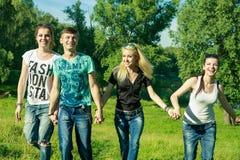 Gente, libertad, felicidad, y concepto adolescente - el grupo de amigos felices sale y diversión en un fondo de árboles verdes fotografía de archivo libre de regalías
