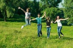 Gente, libertad, felicidad, y concepto adolescente grupo de amigos felices que llevan las gafas de sol que saltan el alto fondo d Imagenes de archivo