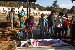 Gente local durante la ceremonia de la cremación a lo largo del río santo de Bagmati en Bhasmeshvar Ghat en el templo de Pashupat Fotos de archivo