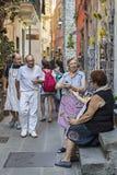 Gente local en la calle estrecha del pueblo colorido de Corniglia, Italia fotos de archivo