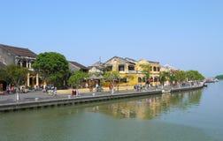 Gente locale, barche, case gialle dal fiume e turisti nella città antica di Hoi An immagini stock