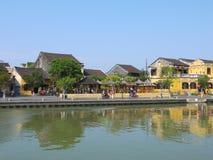 Gente locale, barche, case gialle dal fiume e turisti nella città antica di Hoi An fotografia stock libera da diritti