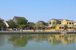 Gente locale, barche, case gialle dal fiume e turisti nella città antica di Hoi An fotografia stock