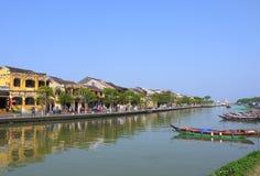 Gente locale, barche, case gialle dal fiume e turisti nella città antica di Hoi An fotografie stock libere da diritti