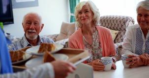 Gente mayor caucásica activa que sonríe en la mesa de comedor en la clínica de reposo 4k almacen de metraje de vídeo